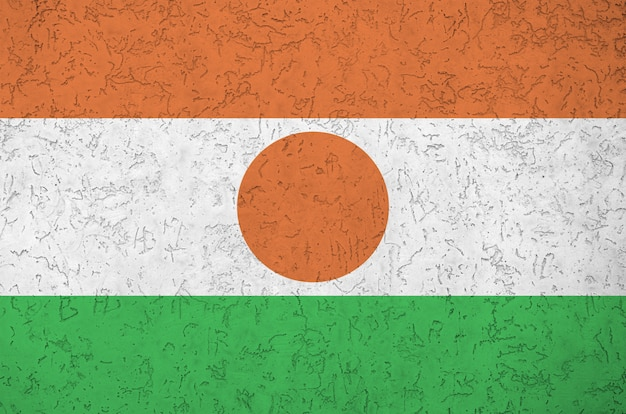 Niger flag depicted in bright paint colors on old relief plastering wall. textured banner on rough background