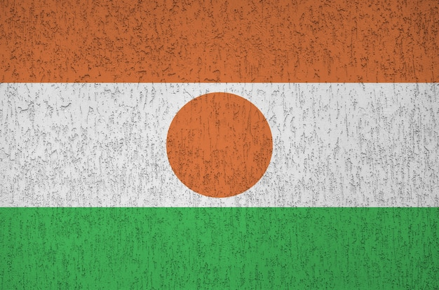 Niger flag depicted in bright paint colors on old relief plastering wall.