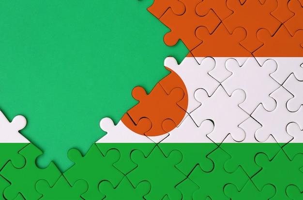 니제르 국기는 왼쪽에 무료 녹색 복사 공간이있는 완성 된 직소 퍼즐에 그려져 있습니다.