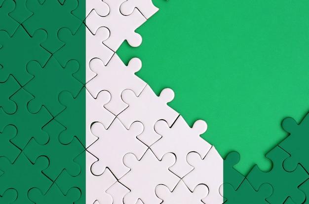 나이지리아 국기는 오른쪽에 무료 녹색 복사 공간이있는 완성 된 직소 퍼즐에 그려져 있습니다.