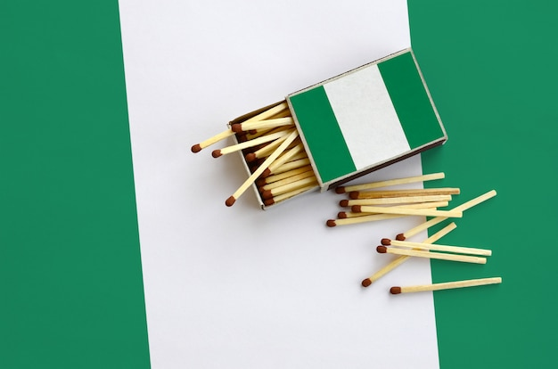 Nigeria flag  is shown on an open matchbox, from which several matches fall and lies on a large flag