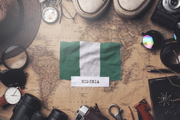Nigeria flag between traveler's accessories on old vintage map. overhead shot