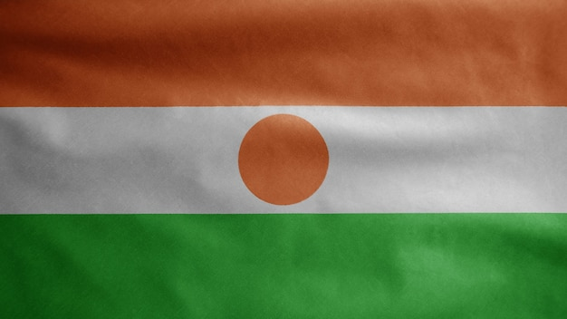 Nigerien flag waving on wind. niger banner blowing smooth silk. cloth fabric texture ensign