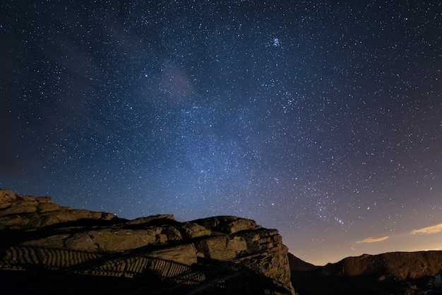 Night on the alps under starry sky and the majestic rocky cliffs on the italian alps