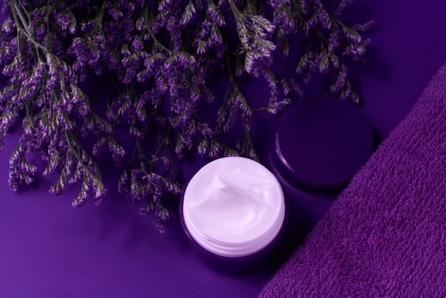 Night anti wrinkle anti-aging  cream body care and face care hygiene moisture lotion with purple flowers in plastic jar with towel on purple background.