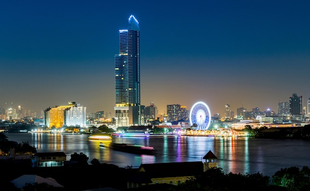 Night architecture business office building and ferris wheel in bangkok