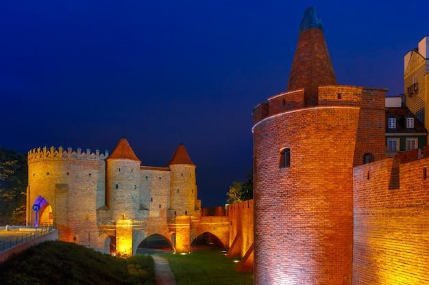 ポーランド、ワルシャワの旧市街の夜のバービカン