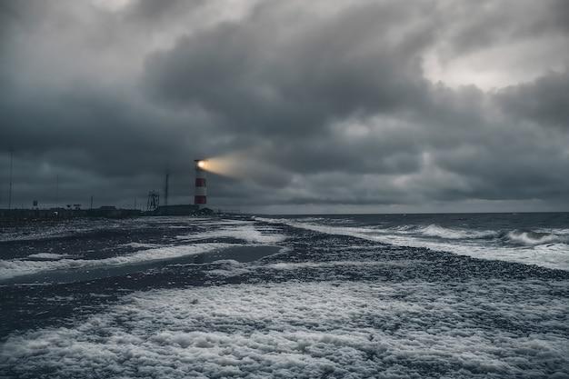 Ночной маяк. маяк на берегу бушующего белого моря на кольском полуострове. кандалакшский залив.
