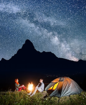 Night camping. happy couple backpackers sitting by bonfire and tent under incredibly beautiful starry sky. silhouette of the high mountains and village in the valley in the background. long exposure
