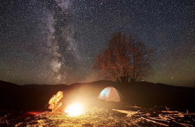 ナイトキャンプ。星空の下でキャンプファイヤーの近くで休んでいるハイカー