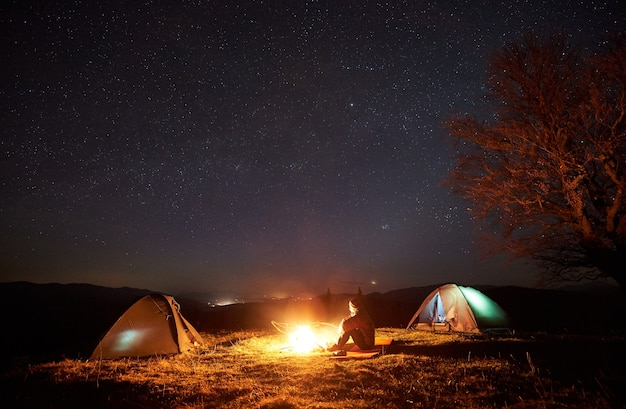 Night camping. hikers resting near campfire under starry sky