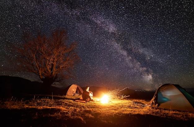 야간 캠핑. 별이 빛나는 하늘 아래 모닥불 근처에서 쉬고 등산객