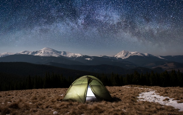 Night camping. illuminated tourist tent under beautiful night sky full of stars and milky way