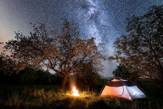 ナイトキャンプ。月と木と夜空の下でキャンプファイヤーの近くに照らされた観光テント