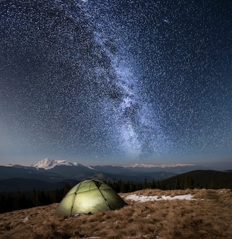 夜のキャンプ。星と天の川でいっぱいの美しい夜空の下で照らされた観光テント。雪に覆われた山と森を背景に