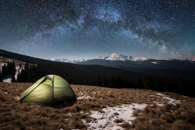 Ночной кемпинг. освещенная туристическая палатка под красивым ночным небом, полным звезд и млечного пути. на фоне заснеженных гор и лесов