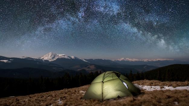 夜のキャンプ。星と天の川でいっぱいの美しい夜空の下で照らされた観光テント