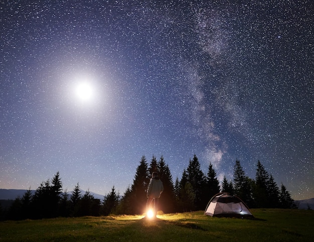 별이 빛나는 하늘과 은하수 아래 산에서 야영하는 밤