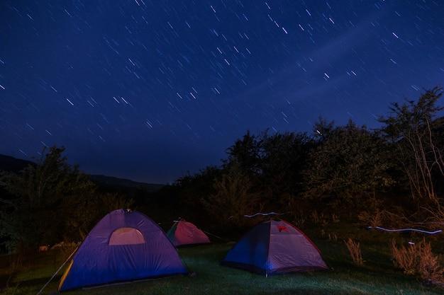 Ночной кемпинг в горах, длинная выдержка звезд на небе фото. тема праздников дикой природы.