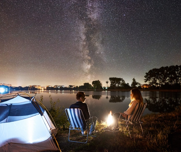 Night camping on lake shore. man and woman hikers sitting on chairs near campfire, tent. couple tourists enjoying night sky full of stars and milky way, quiet water surface, city lights