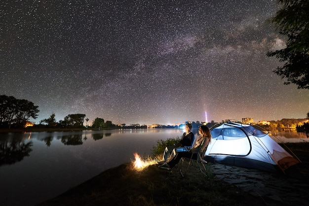 Night camping on lake shore. man and woman sitting on chairs near bonfire and glowing tent, enjoying view of evening sky full of stars and milky way, quiet water surface, luminous town
