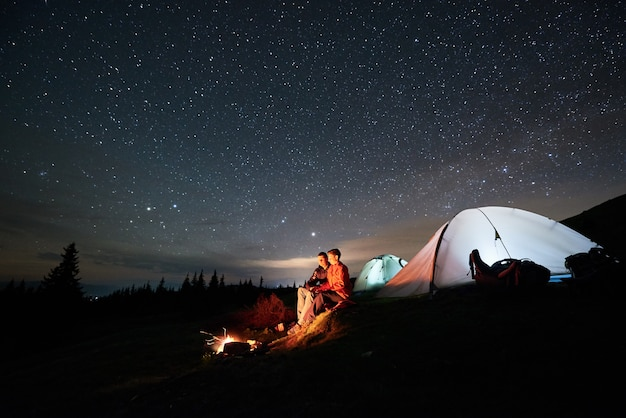 Night camping in the mountains. man and woman tourists sitting at a campfire near two illuminated tents under starry sky at night