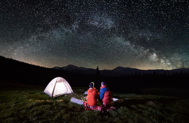 Night camping in the mountains. rear view of romantic couple tourists have a rest at a campfire near illuminated tent under amazing night sky full of stars and milky way