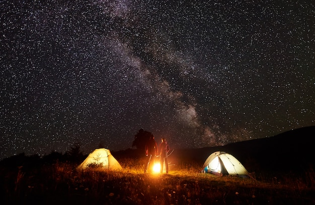 Night camping in the mountains. silhouettes of man and woman standing in front of shining tents, holding hands under amazing dark starry sky and milky way