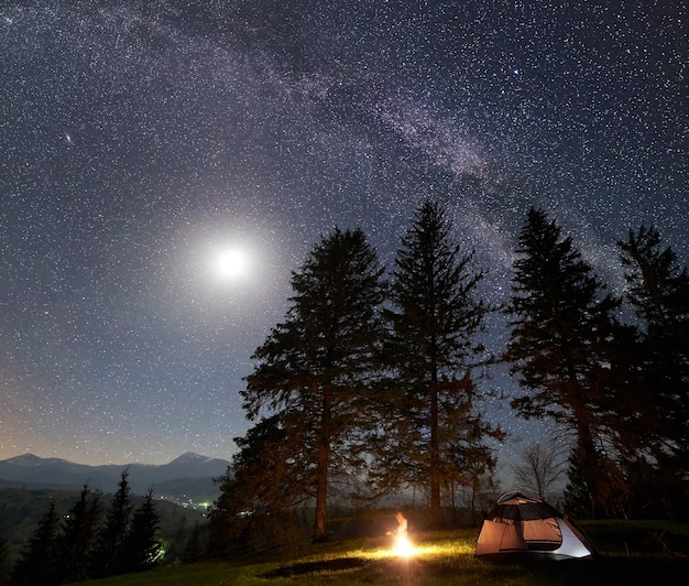 Night camping in mountains under starry sky and milky way