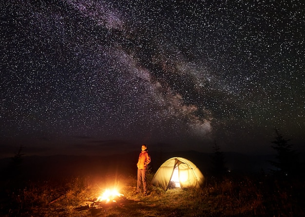Night camping in mountains. woman resting near illuminated tent and brightly burning bonfire on deep dark sky with lot of bright sparkling stars and milky way