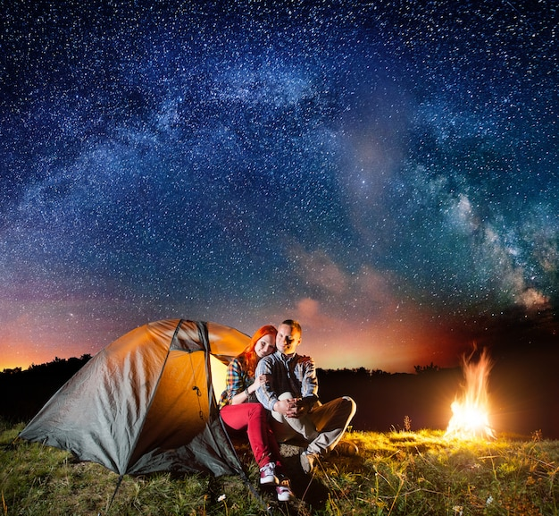 Night camping. tourists sitting in front tent near campfire under starry sky