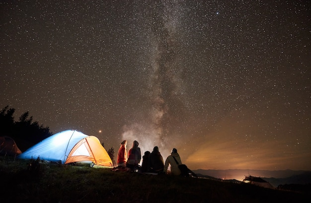 Night camping with people around campfire under night starry sky