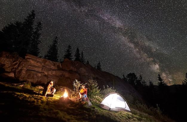 밤 별이 빛나는 하늘 아래 모닥불 주위 사람들과 밤 캠핑