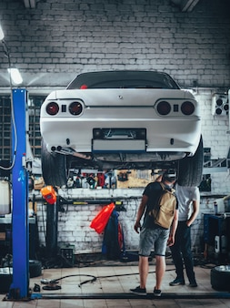 Night car service. sport drift car on the lift. suspension inspection and repair
