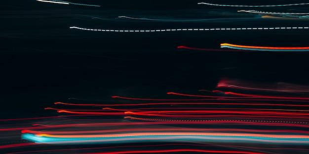 Night city in motion defocus, red lights, horizontal traffic. abstract blurred bright lights background.