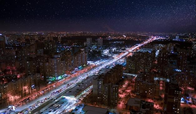夜の街の近所。ドローンビュー。カラフルなライトが通りや建物を照らします。素晴らしい街の夜の風景。