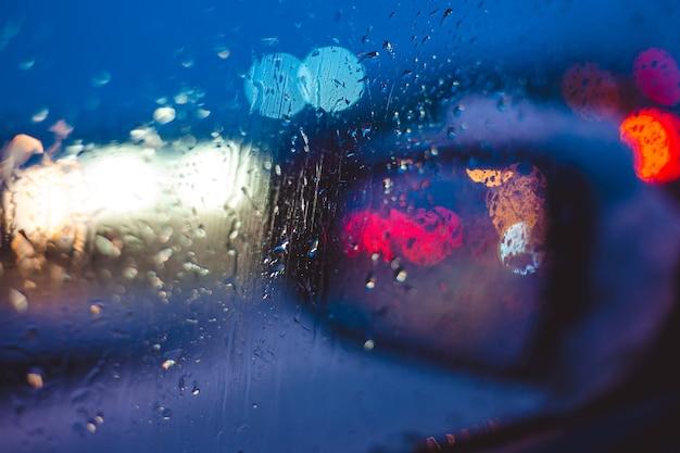 Ночная городская дорога через лобовое стекло автомобилей абстрактный фон капли воды на стекле огни и дождь.