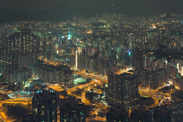 Night city view from a height to buildings in the lights and roads of the city. hong kong.