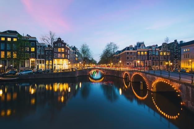 Ночной вид на город в амстердаме, нидерланды. канал и типичные голландские дома