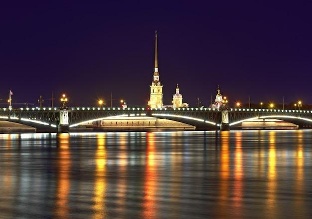 Ночной город вид на троицкий мост и петропавловский собор в отражении ночных огней в водах невы. архитектура xviii века.
