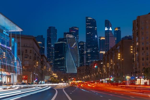 Ночной городской пейзаж небоскребов с темным небом и светлыми тропами на дороге