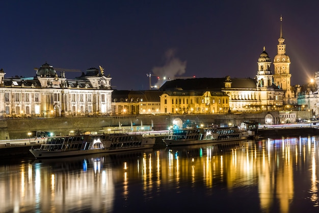 Night cityscape view of historic buildings with reflections in elbe river in the center of dresden (germany).