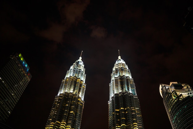 Night cityscape with famous twin towers petrochemical company petronas in kuala lumpur
