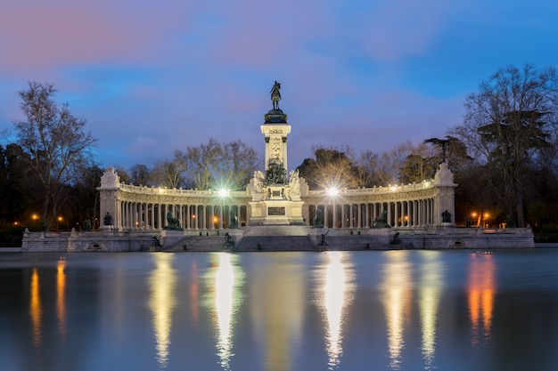 Night cityscape with lights at the memorial in retiro city park, madrid, spain.