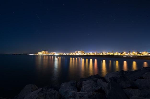 Ночной городской пейзаж с морем и скалами на переднем плане и ночным звездным небом, ночной городской пейзаж испанского города. путешествие по европе, вид на карту с городскими огнями и набережной ночью