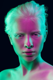 Night. close up portrait of beautiful albino girl on dark background in neon light. blonde female model with dreamlike make-up and well-kept skin. concept of beauty, cosmetics, style, fashion.