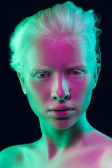 Ночь. закройте вверх по портрету красивой девушки-альбиноса на темном фоне в неоновом свете. блондинка-модель с сказочным макияжем и ухоженной кожей. понятие красоты, косметики, стиля, моды.