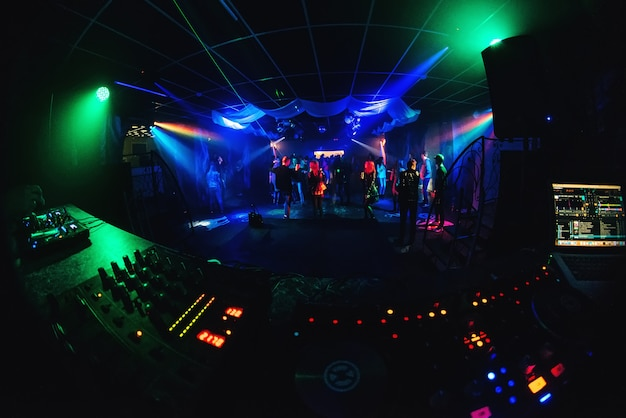 Night club with dancing people on dance floor, revelers at a party and music board of the dj