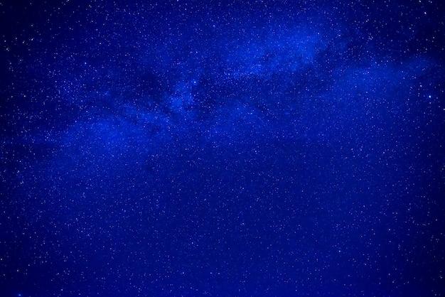 Ночное темно-синее небо с множеством звезд и галактикой млечный путь