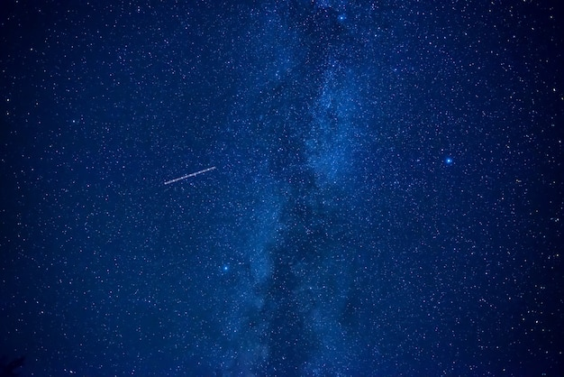 Night dark blue sky with many stars of milky way galaxy and flying satellite